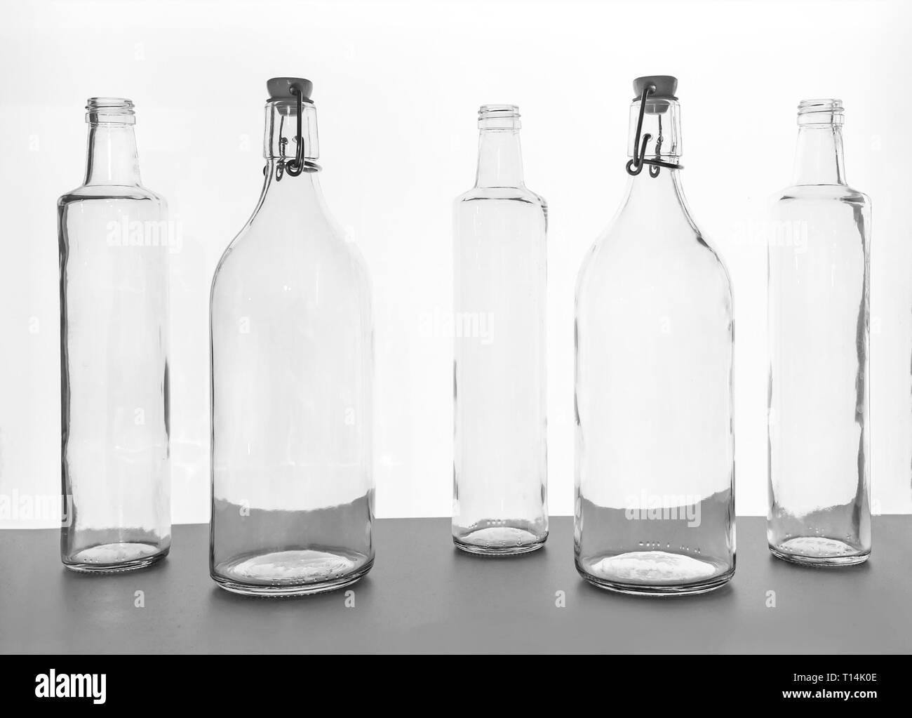 Empty transparent glass bottles silhouette on the white illuminate from behind background - Stock Image
