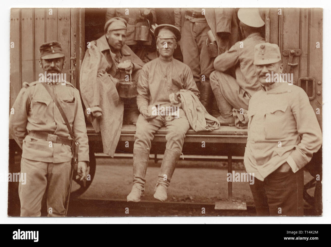 Russian prisoners of war pictured with the Austrian convoy while being transported during the First World War in the railway carriage probably on some railway station in the modern-day Czech Republic. Black and white vintage photograph by an unknown photographer. Courtesy of the Azoor Photo Collection. Stock Photo