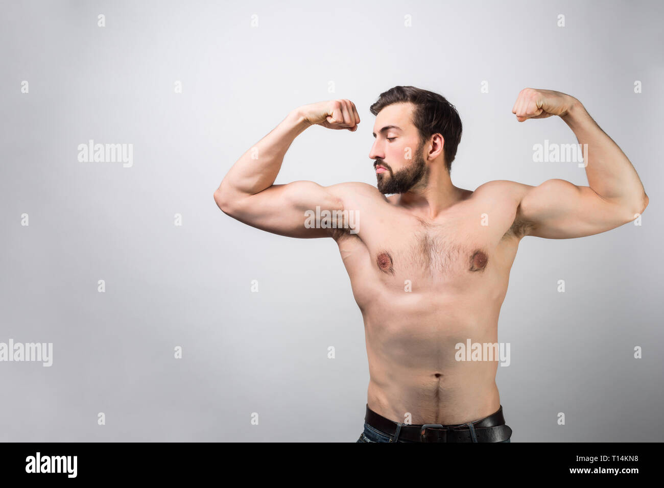 348614f0f Strong and powerful guy without a shirt is standing at white wall and  posing. He