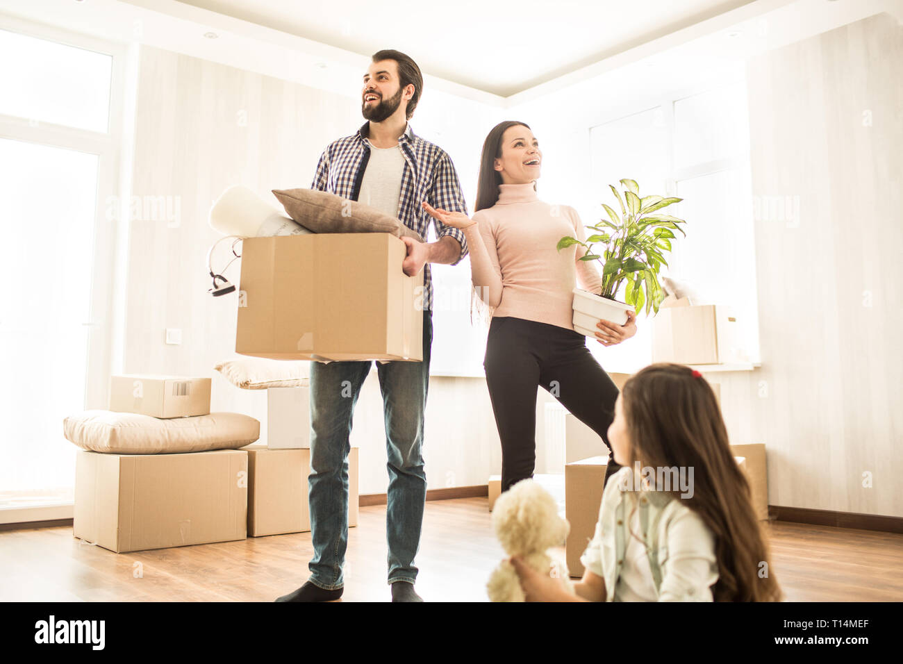 Man and woman are standing close to each other and looking to different sides of room with an amazed sight. Their child is sitting on the floor with t Stock Photo