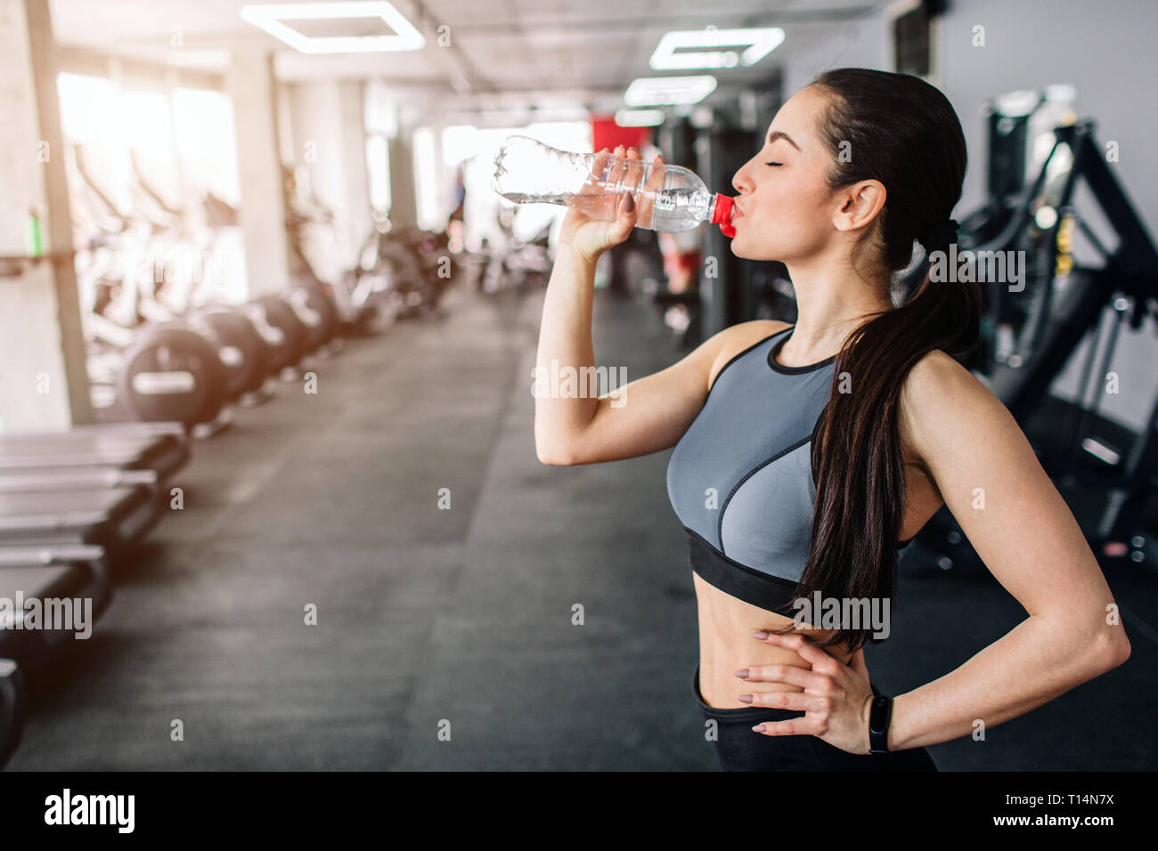 Close up of a beautiful girl drinking water from the bottle. He is having some rest after workout. Cut view. Stock Photo
