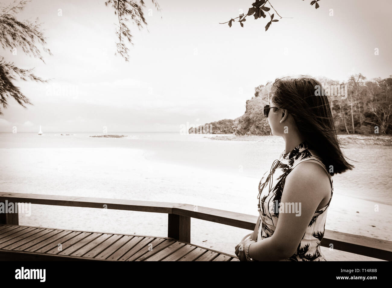 Woman tourist wearing sunglasse looking at the beach and sea in summer on Tarutao island National Park, Satun, Thailand, in two tone black and white c - Stock Image