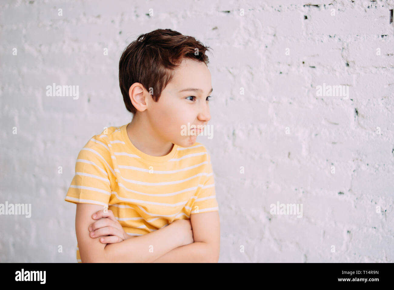 Cute tween angry boy with funny face in yellow t-shirt isolated on white brick wall background - Stock Image