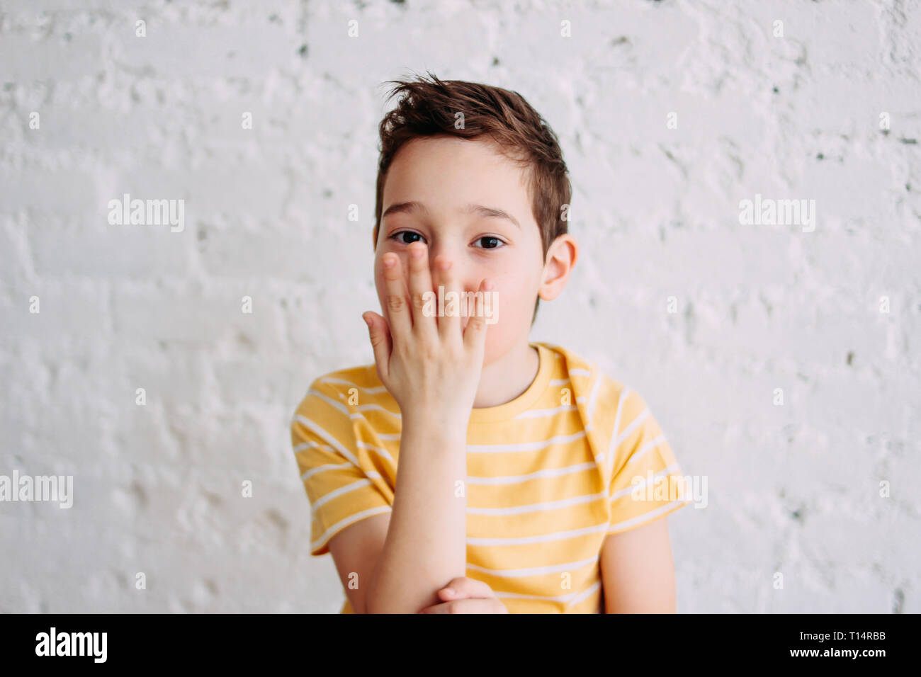 Cute tween boy in yellow t-shirt making kiss by hands isolated on the white wall background - Stock Image