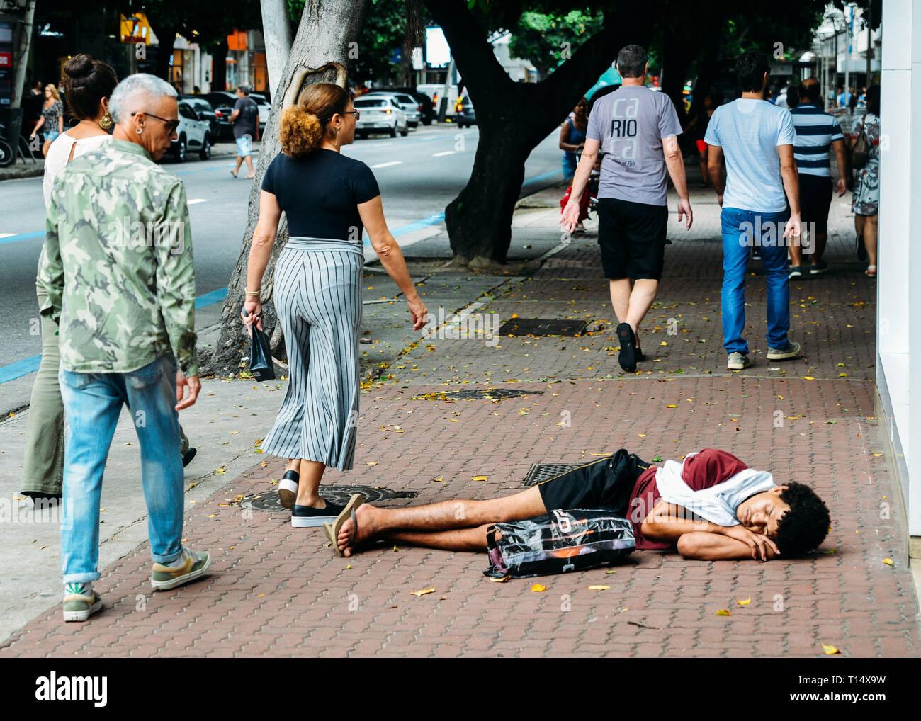 Rio de Janeiro, Brazil, March 23, 2019: Homeless young man sleeping rough while pedestrians walk next to him on busy pedestrian sidewalk in the wealth Stock Photo