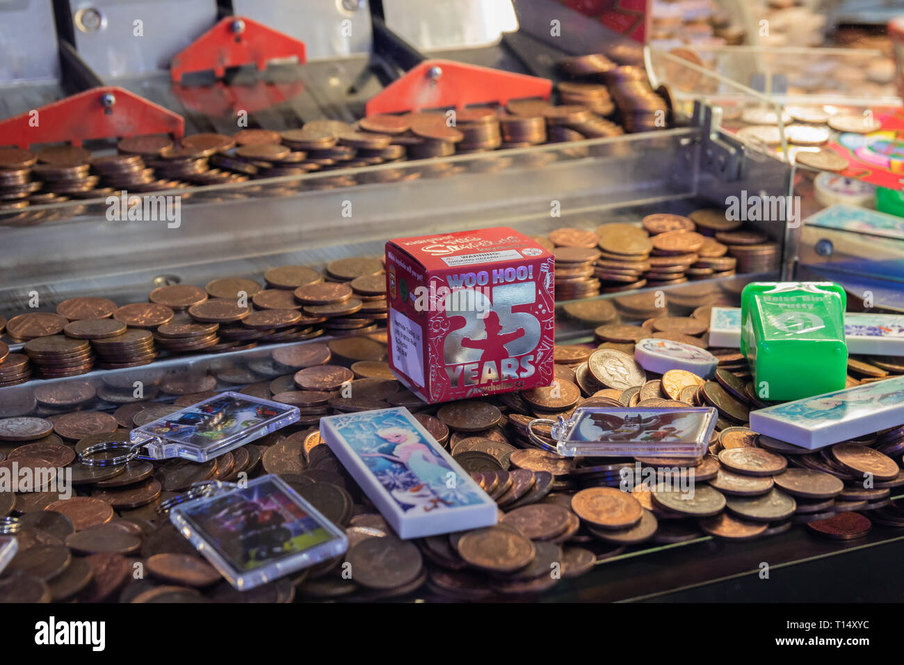 Close up of twp pence pieces in a coin push machine in the arcade - Stock Image