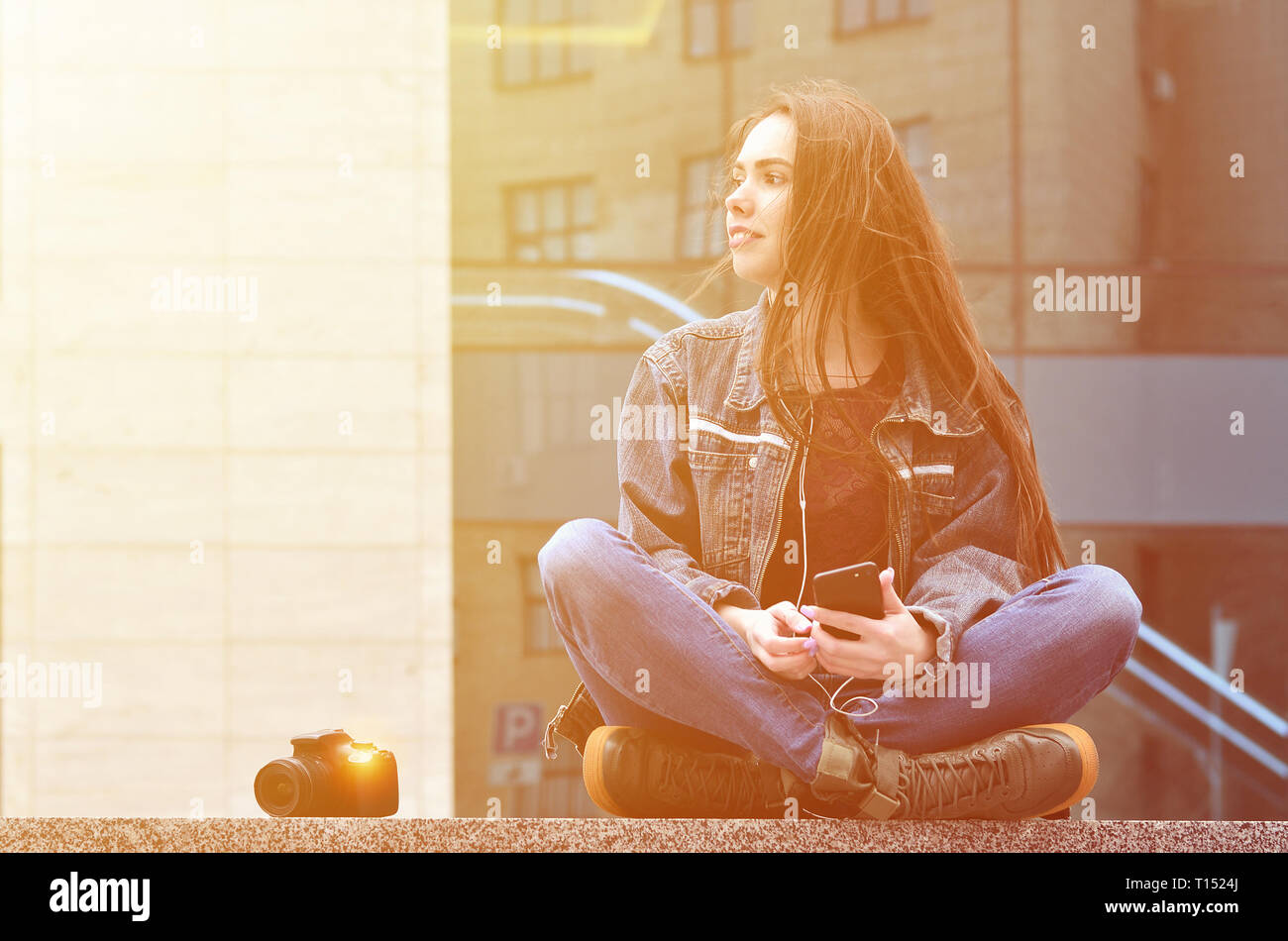 A young female photographer in jeans clothes uses a smartphone, sit on a granite parapet against a glazed office building. Concept for lessons or onli - Stock Image