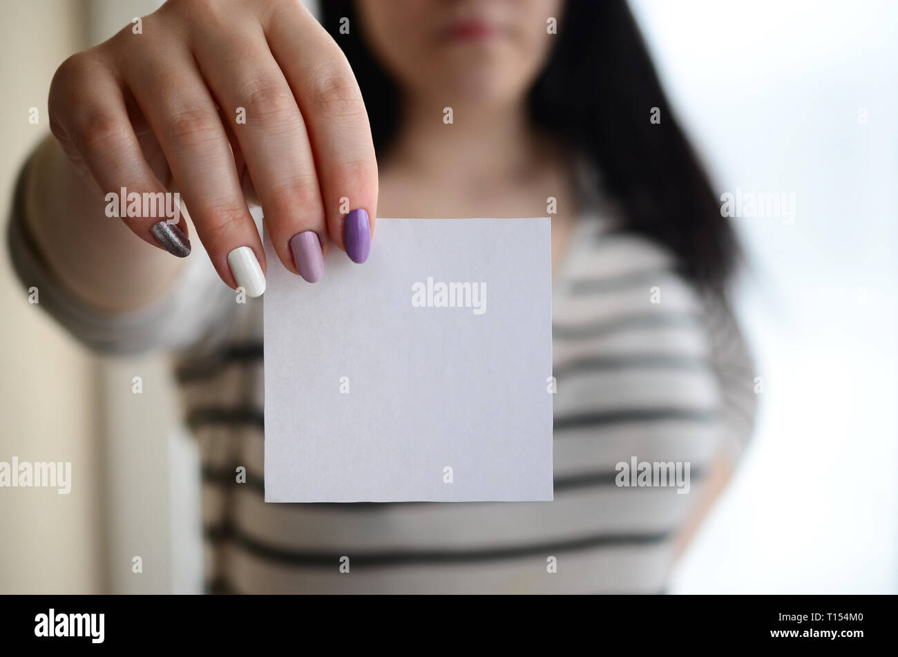Young sad girl shows a white sticker. Caucasian brunette holding a blank sheet of paper as a template for your text Stock Photo