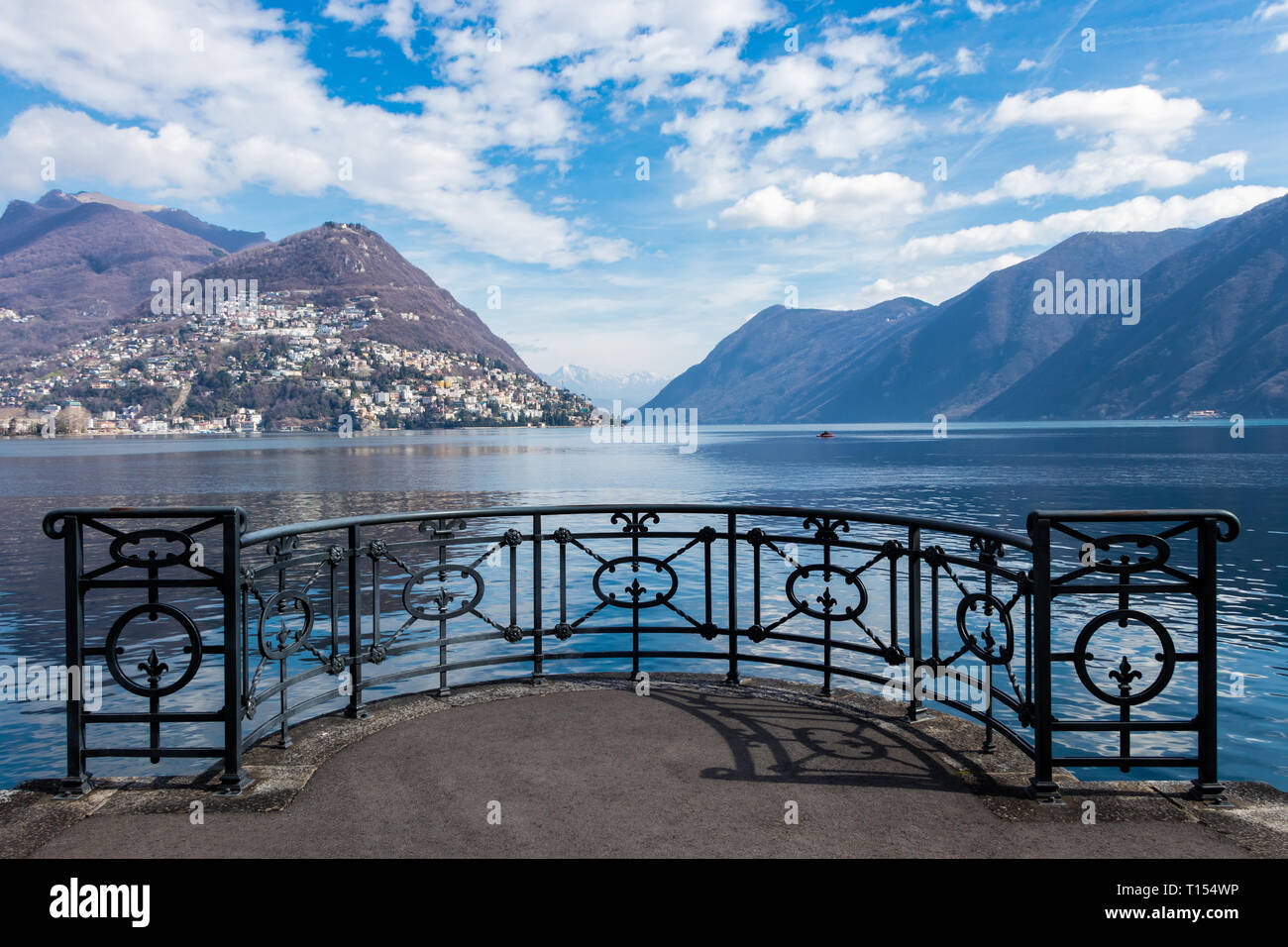 Black fence in perspective on the shores of Lake Lugano, Ticino canton of Switzerland Stock Photo