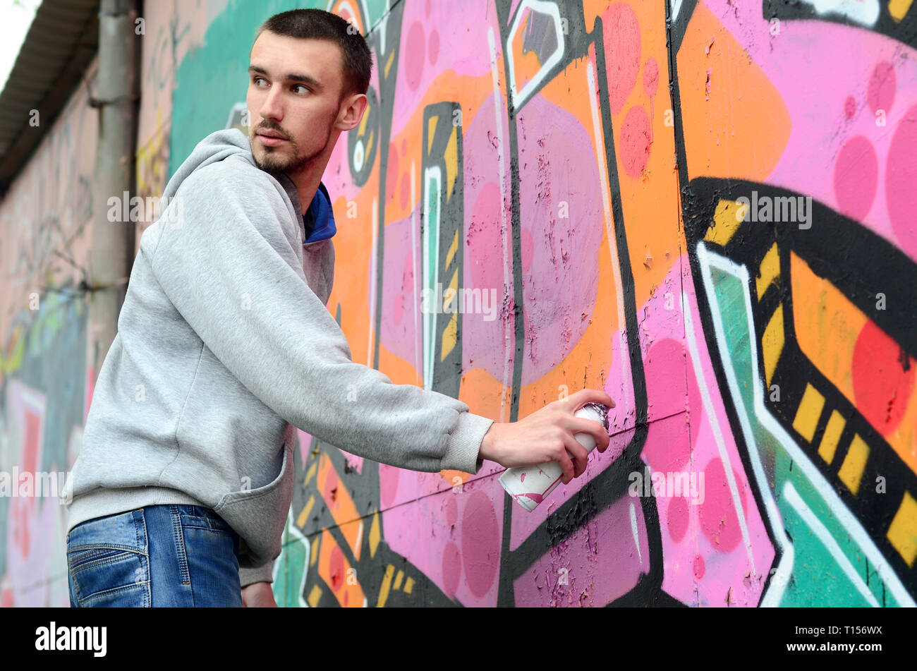 A young graffiti artist looks around while drawing. Vandal tries to be undetected while drawing the picture on the wall. The concept of hooliganism an - Stock Image