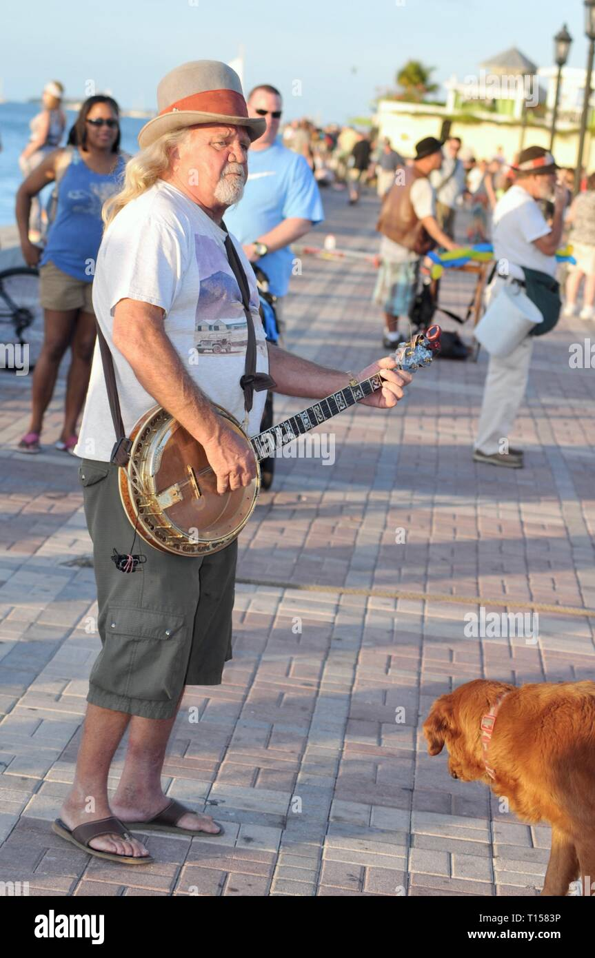 Male musician street performer playing banjo for crowds of tourists at Mallory Square on Key West, Florida Keys, Florida, USA Stock Photo