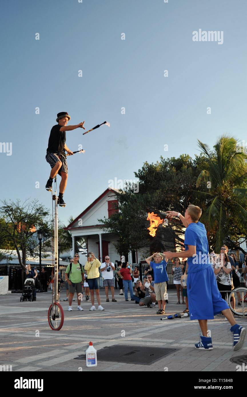 Male street performer pedaling on a unicycle while juggling, entertaining crowds, at Mallory Square on Key West, Florida Keys, Florida, USA Stock Photo
