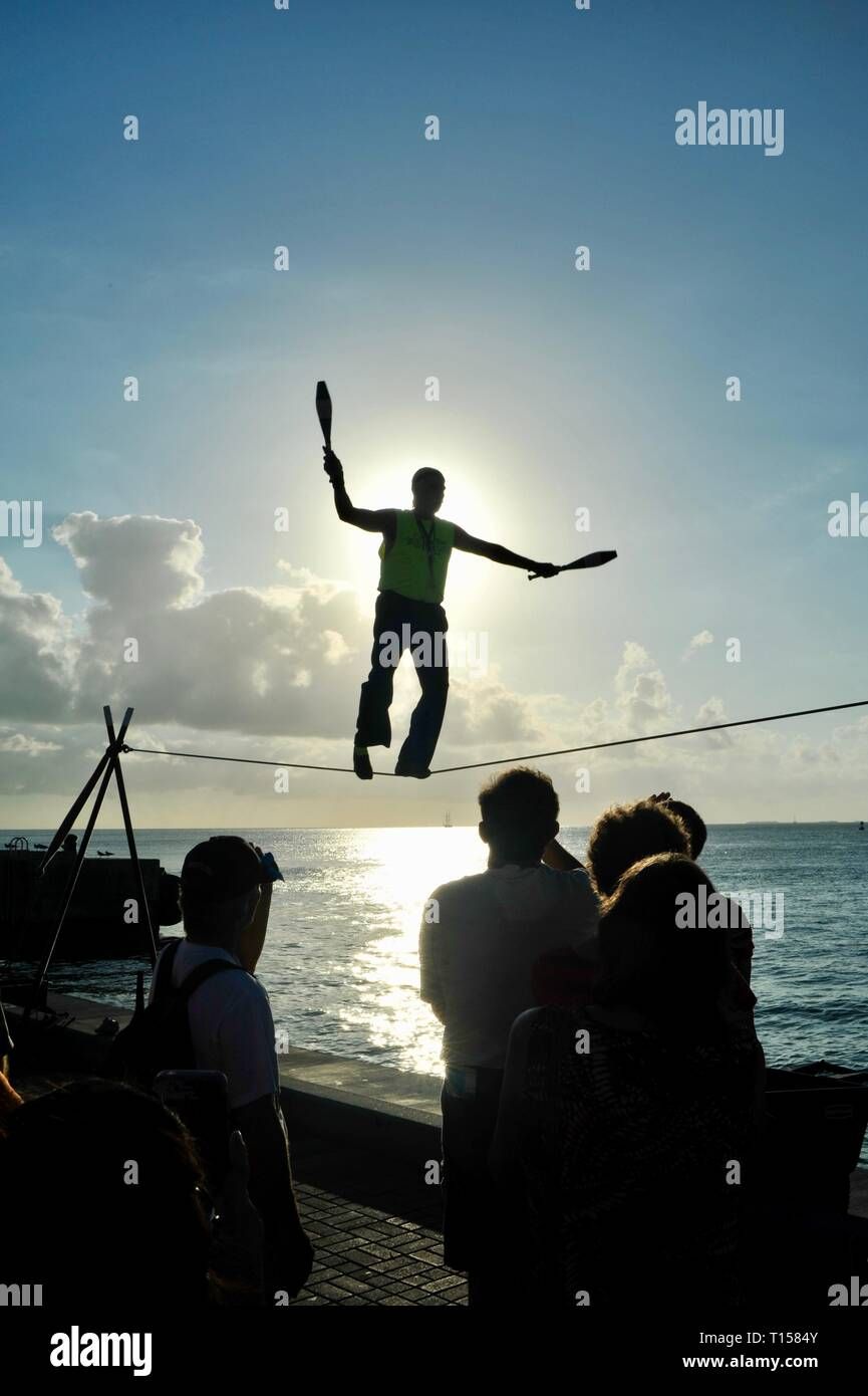 Male street performer balancing on tightrope while juggling, entertain crowds, Mallory Square Sunset Celebration, Key West, Florida Keys, Florida, USA Stock Photo