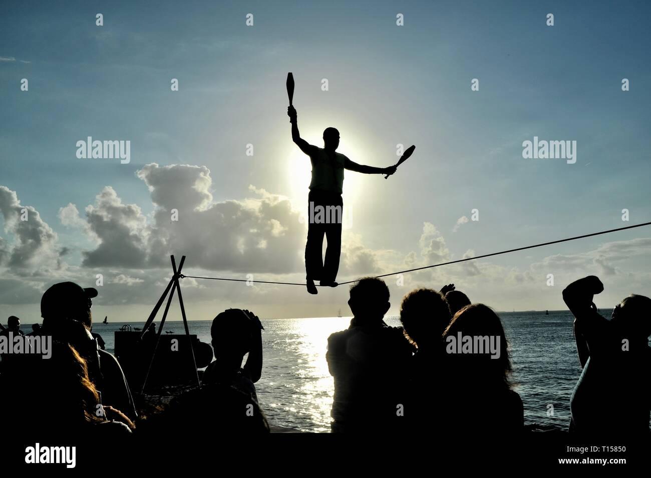 Male street performer balancing on tightrope while juggling, entertain crowds, Mallory Square Sunset Celebration, Key West, Florida Keys, Florida, USA Stock Photo