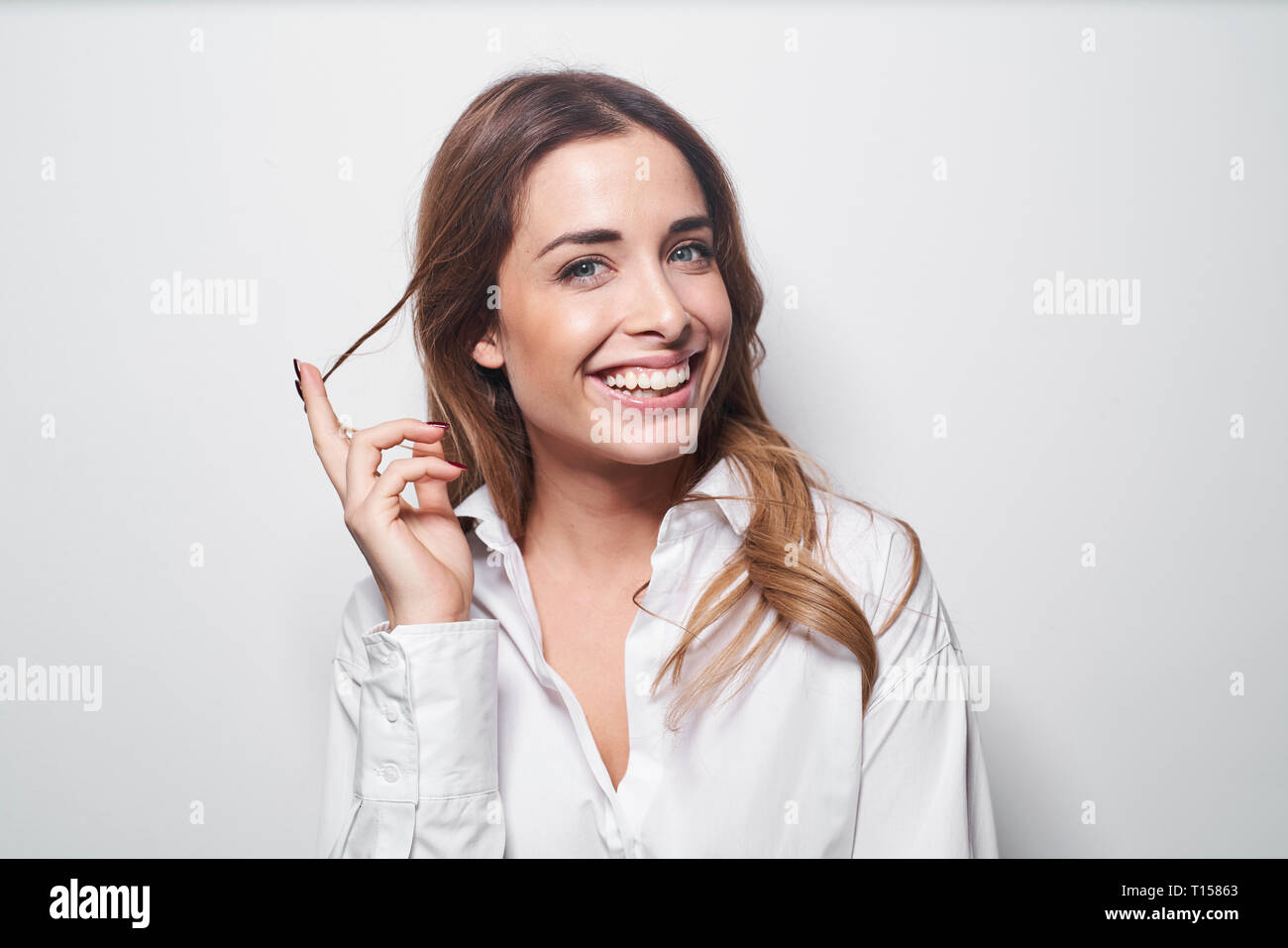 Portrait of laughing young woman twirling strand of hair - Stock Image
