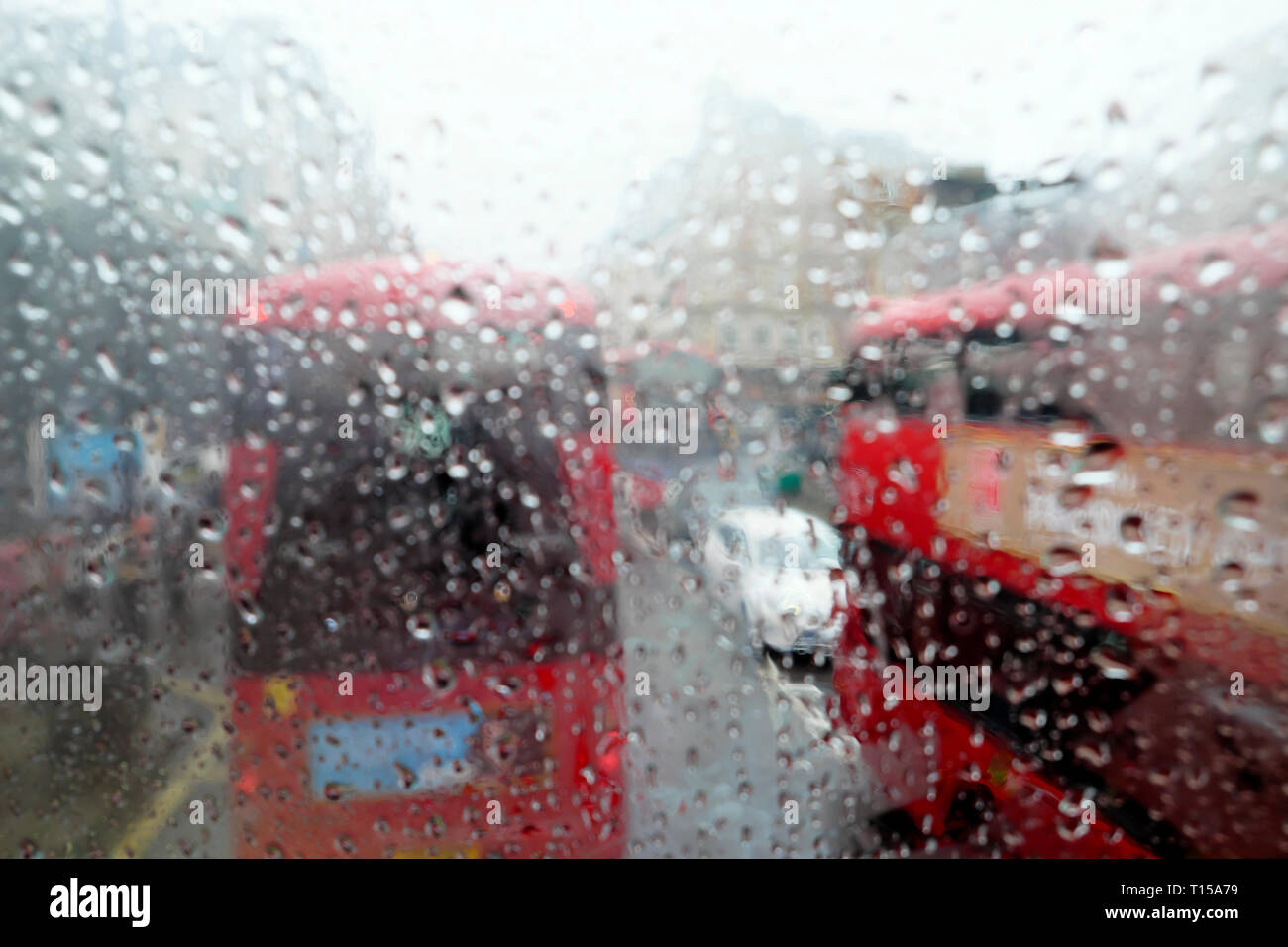 A view of double decker red buses in traffic view from top of bus interior raindrops on window on rainy day in London England UK  KATHY DEWITT Stock Photo
