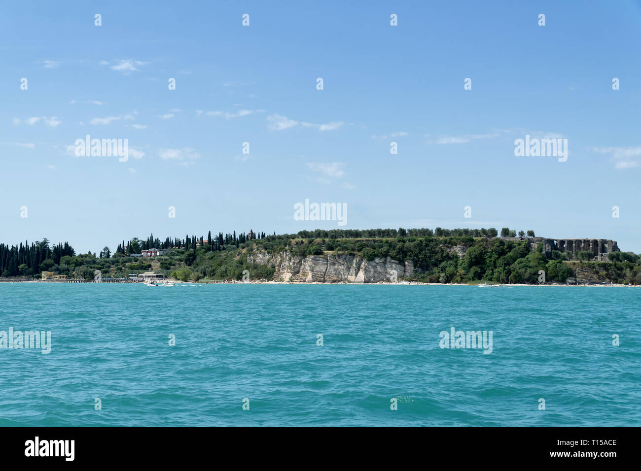 Stony Beach of Sirmione town on Garda Lake with view of Grottoes of Catullus (Grotte di Catullo), the ruins of a Roman villa built at the end of the 1 Stock Photo