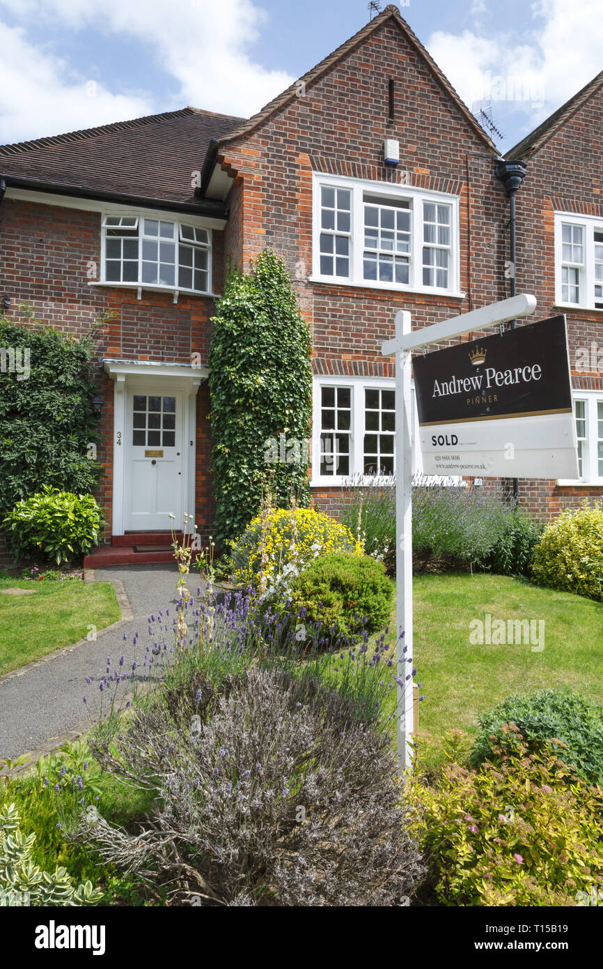 London, UK - July 15, 2014. A London estate agent sold sign is displayed outside a suburban semi-detached house in Pinner, northwest London. - Stock Image