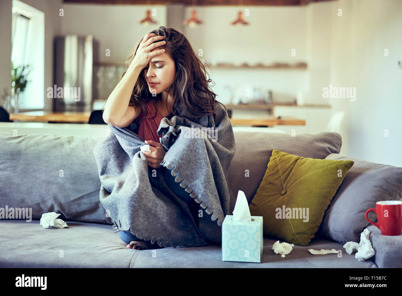 Portrait of sick woman sitting on couch and holding her aching head - Stock Image
