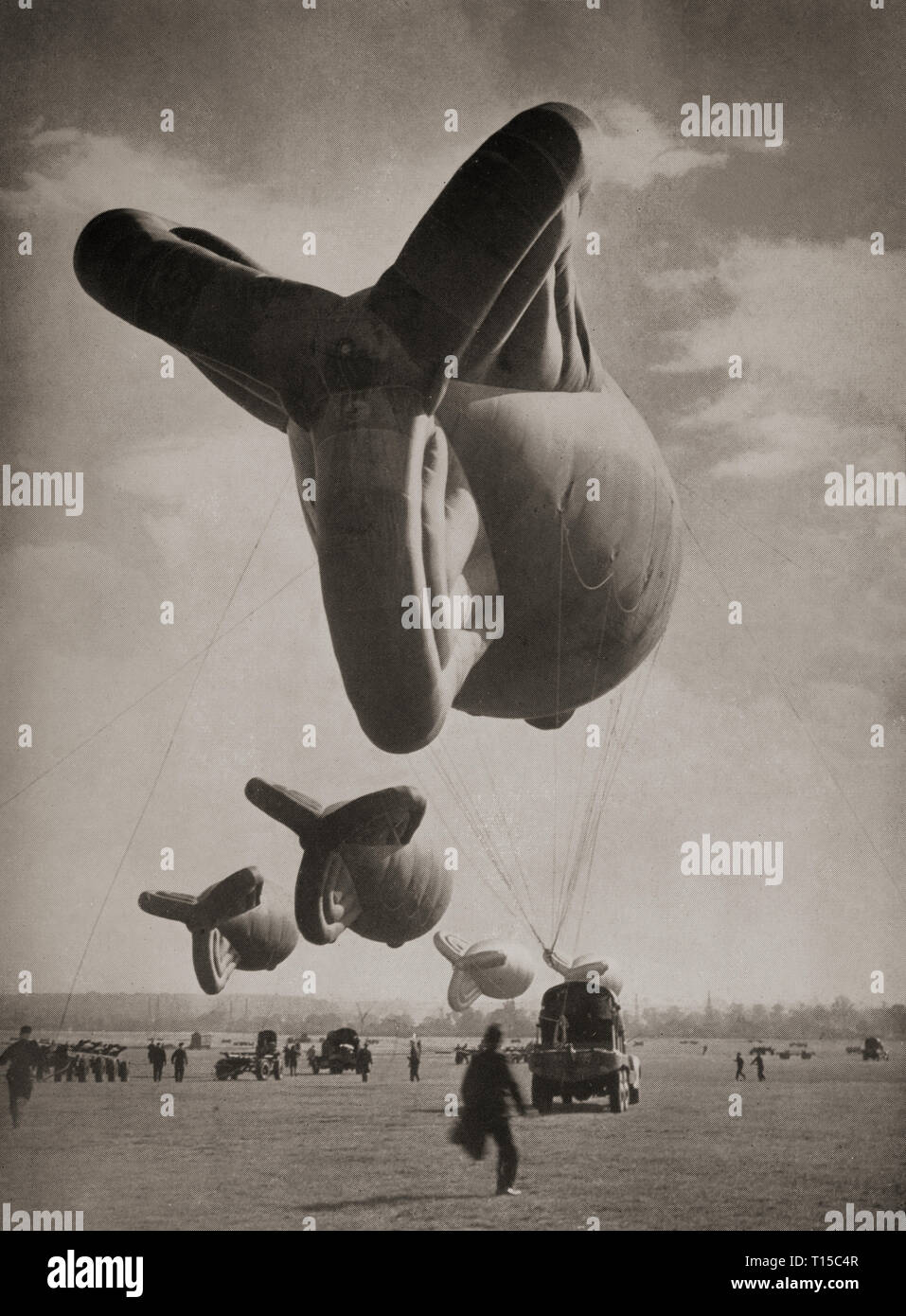Barrage Balloons being towed by their winch vehicles. In 1938 the British Balloon Command was established to protect cities and key targets such as industrial areas, ports and harbours. Balloons were intended to defend against dive bombers flying at heights up to 5,000 feet (1,500 m), forcing them to fly higher and into the range of concentrated anti-aircraft fire—anti-aircraft guns could not traverse fast enough to attack aircraft flying at low altitude and high speed. - Stock Image