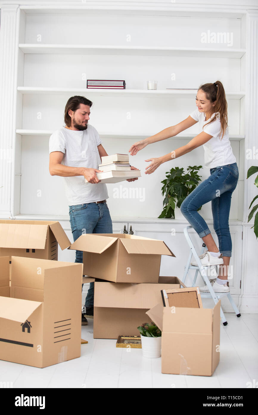Couple unpacking cardboard boxes and furnishing new home - Stock Image