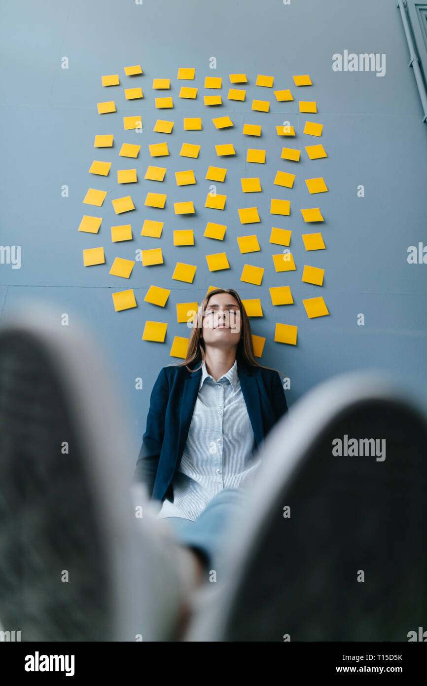 Young businesswoman sitting under data clound, relaxing with eyes closed - Stock Image