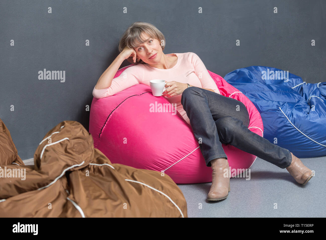 Portrait of woman relaxing with cup of coffee on bean bag in the office - Stock Image