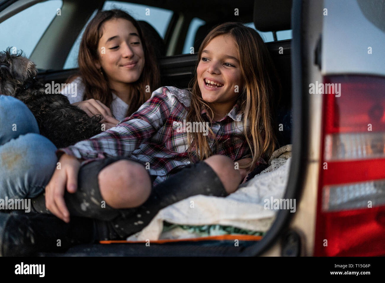 Two sisters in boot of parked car watching sunset - Stock Image