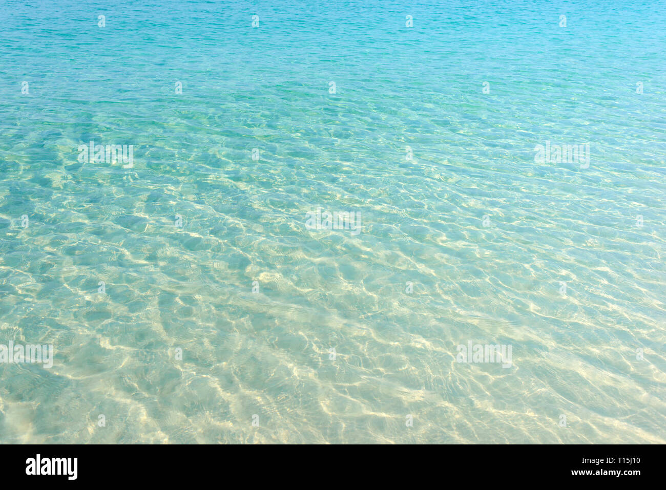 Clear blue water ripple on sandy beach. Sea water reflections surface. Tropical sunny summer day. - Stock Image