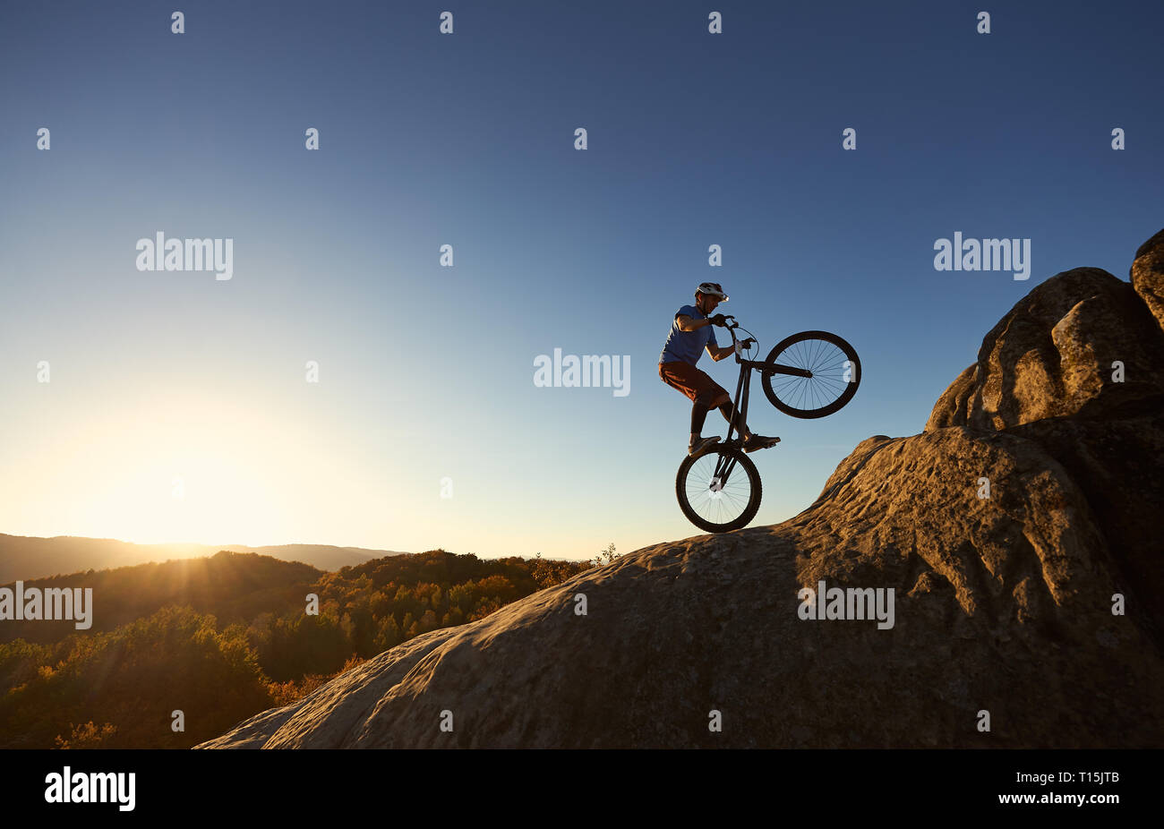 Silhouette of courageous cyclist balancing on back wheel on trial bicycle. Professional sportsman biker making acrobatic stunt on the top of mountain  Stock Photo