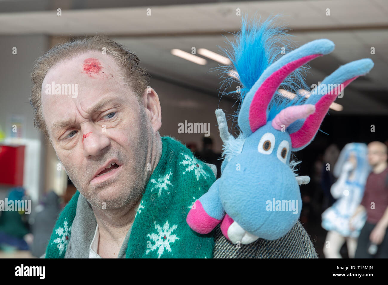 Birmingham, UK. Saturday 23 March 2019. Cosplayers seen in character as Nicholas 'Nick' Sax and unicorn named Happy from the  Netflix hit Happy on the 1st day of the MCM Comic Con Birmingham at the NEC  , © Jason Richardson / Alamy Live News - Stock Image