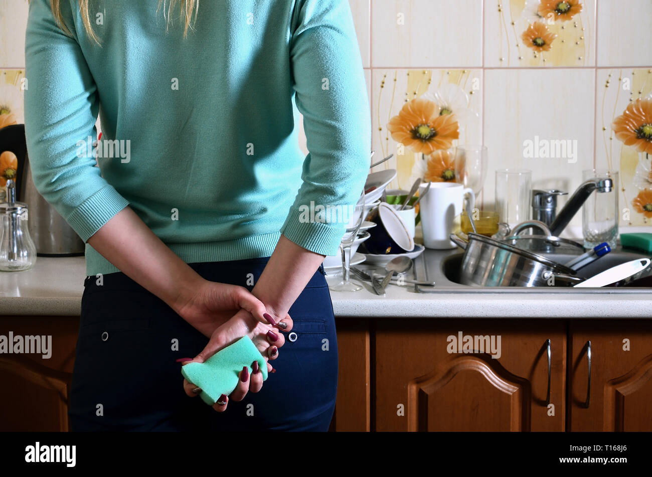 Fragment of the female body at the kitchen counter, filled with a lot of unwashed dishes. The girl is tired of coping with the daily duty of washing d - Stock Image