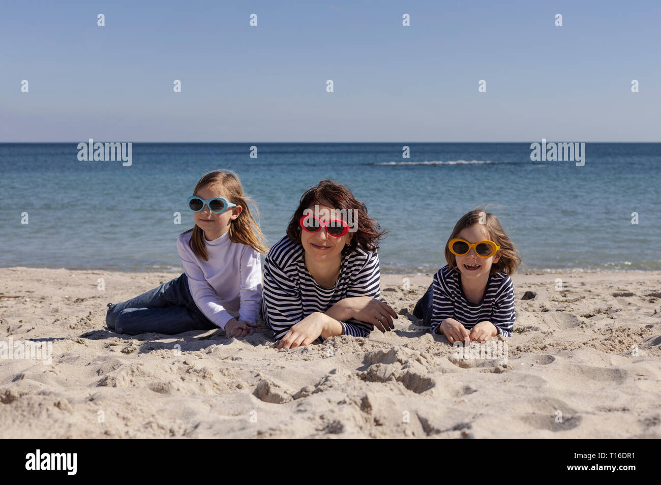 Walk moms with children on the beach. Sisters (8 and 7 years old) and younger brother (3 years old) are playing at sea. Selective focus. Stock Photo