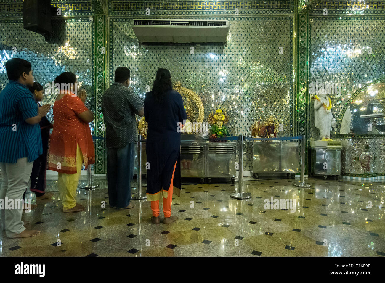 The unique Arulmigu Sri Rajakaliamman Glass Temple in Johor Bahru, Malaysia. The interior is completely covered in glass tiles. Interior and praying. - Stock Image