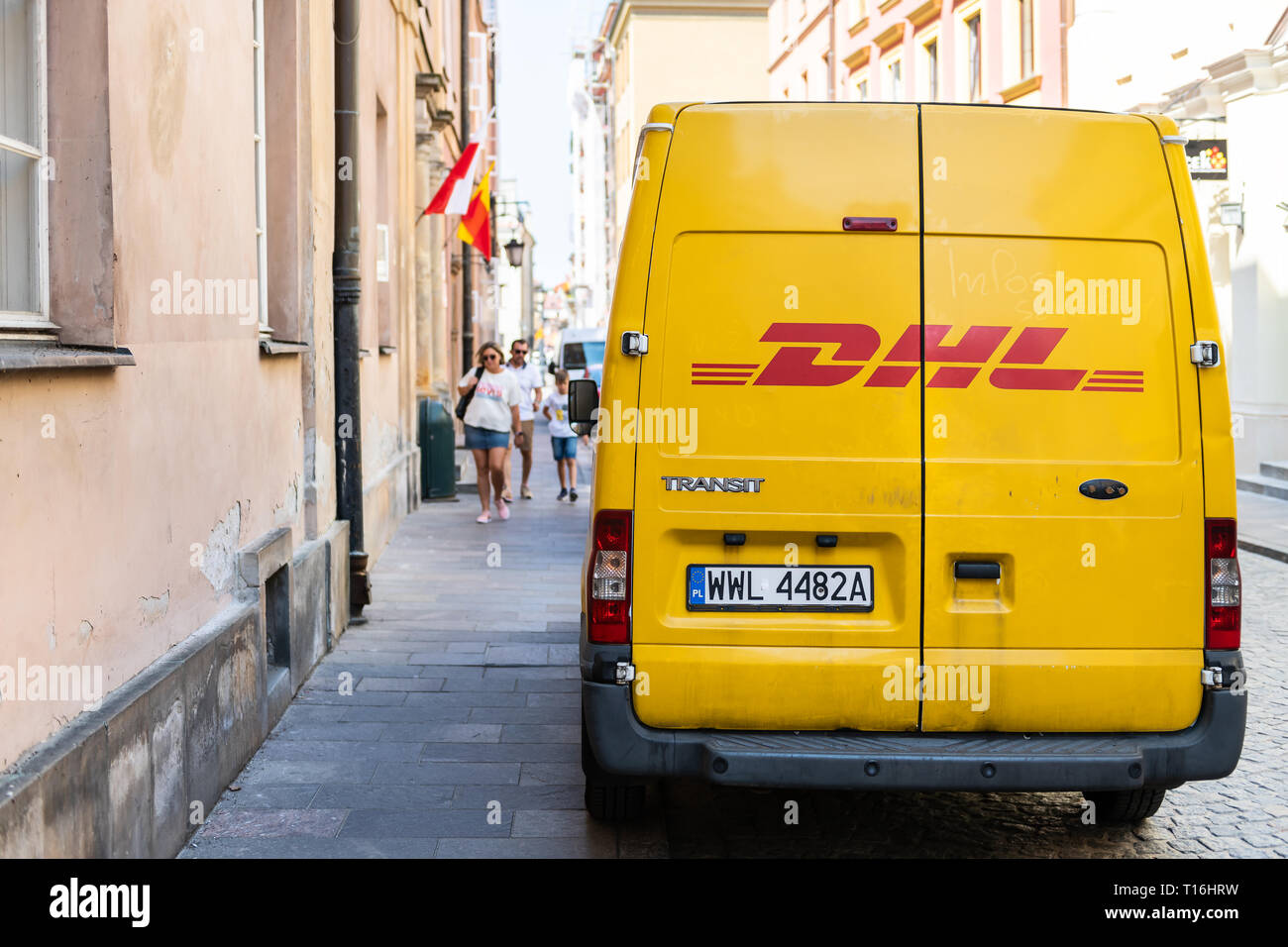 Warsaw, Poland - August 23, 2018: Old town street with closeup of DHL delivery truck in city with yellow color and sign - Stock Image