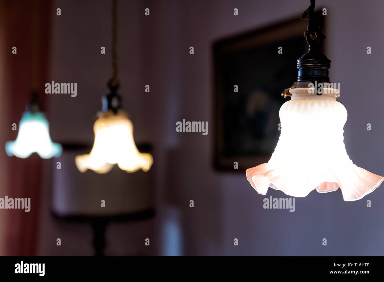 Closeup of three hanging ceiling lamps in home with dark room and