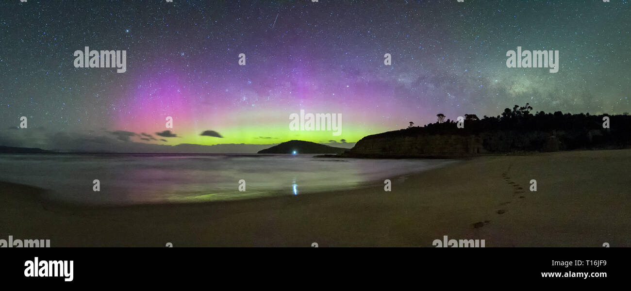 Panorama of a bright and colourful display of the Aurora Australis or Southern Lights, blue and green, with the galactic centre of the Milky Way. - Stock Image