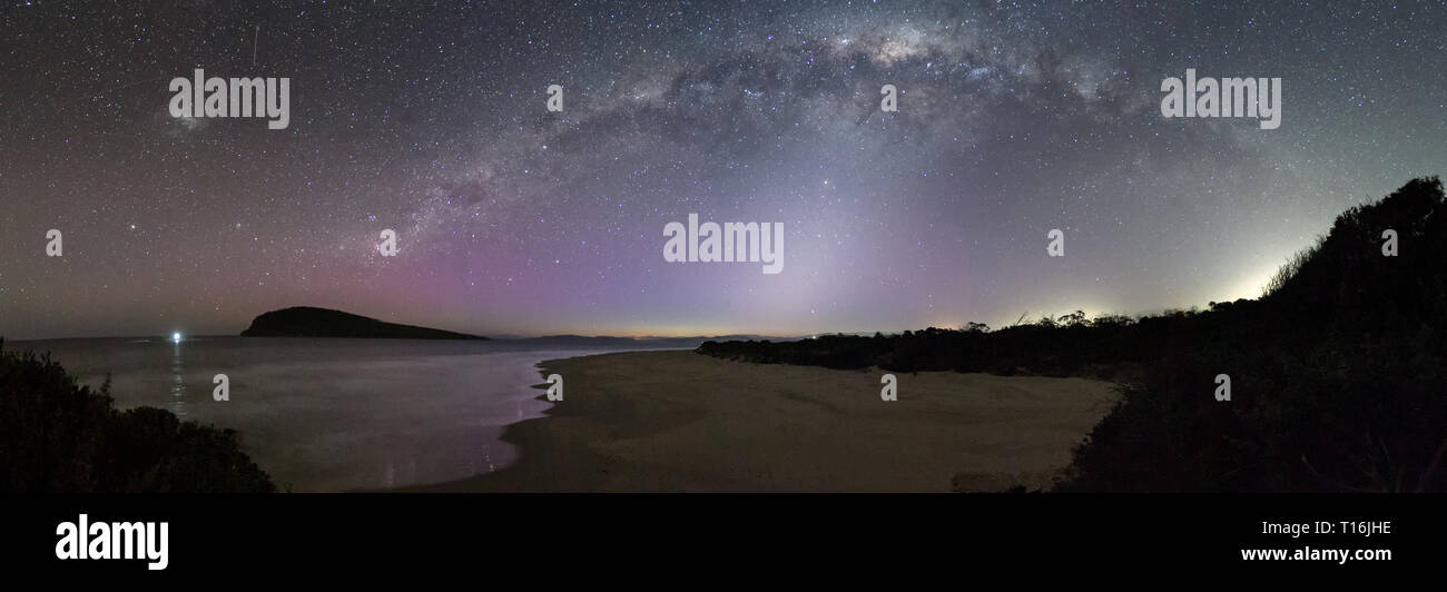 Panorama of the Milky Way with a shaft of Zodiacal light underneath and a feint display of the Aurora Australis or Southern Lights, Tasmania. - Stock Image