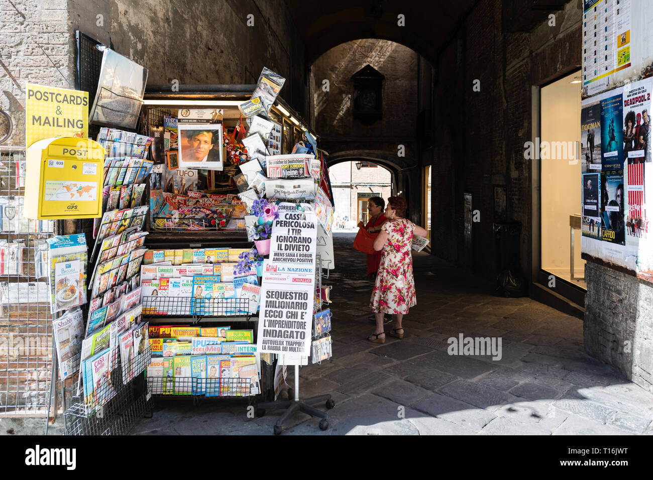 Siena, Italy - August 27, 2018: Historic medieval old town village in Tuscany with shopping souvenirs and map tour travel guide street vendor retail d - Stock Image