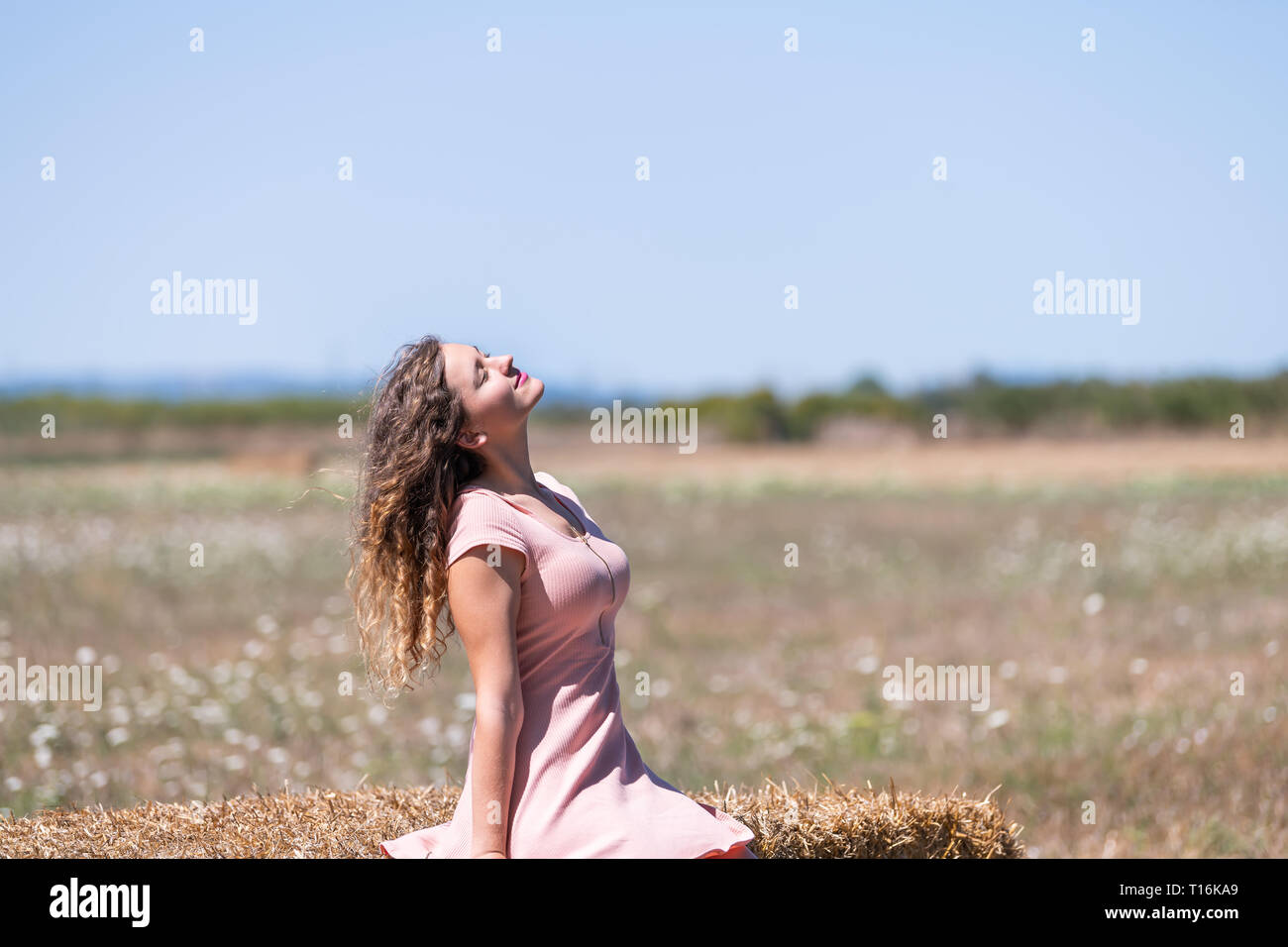 Countryside landscape in Tuscany, Italy with young girl woman happy looking up sitting on hay bale in dress with hair in wind posing model Stock Photo