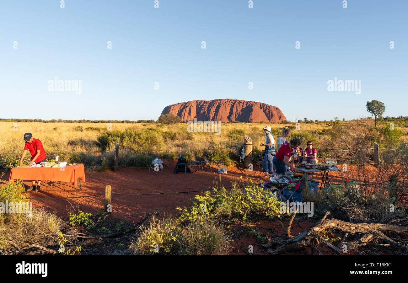 25th December 2018, Sydney NSW Australia : People setting dinner bbq buffet tables at Uluru sunset view point and Ayers rock in background in NT outba - Stock Image