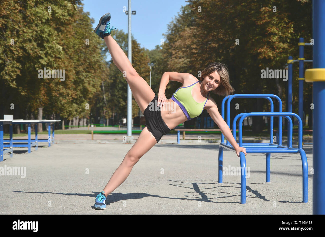 A young caucasian female athlete in bright green sport clothes practicing leg rides on the sports gym for active outdoor recreation. Summer sports and - Stock Image