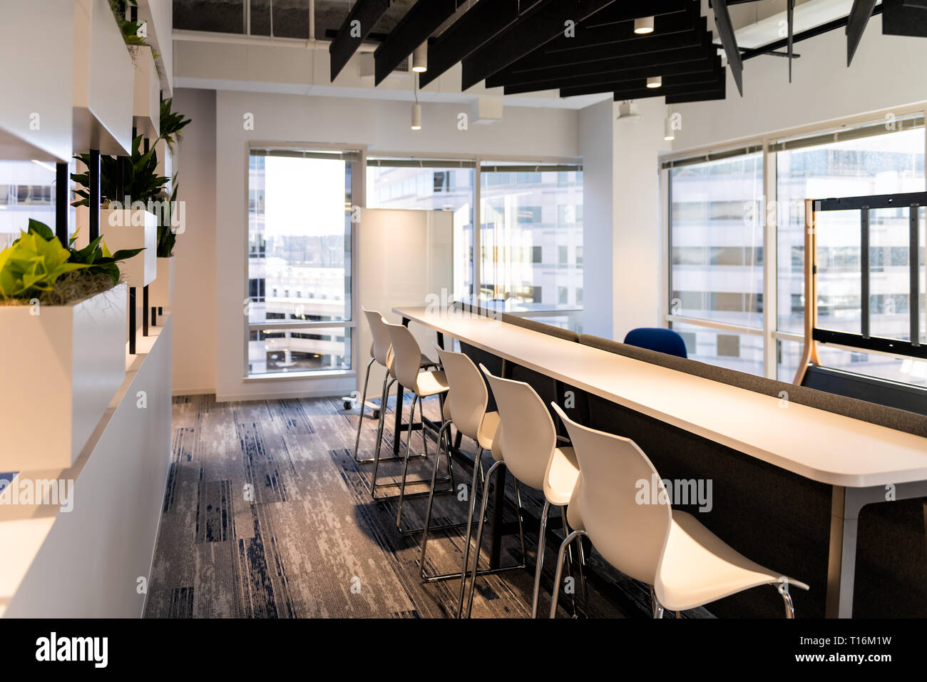 Modern empty office room kitchen bar in building with corporate business table by glass window and presentation screen projector many row chairs nobod - Stock Image