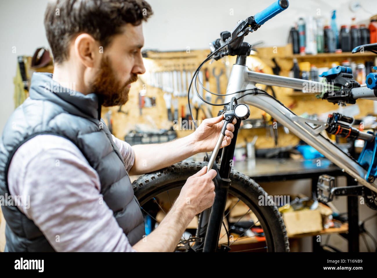 Repairman serving a bicycle, checking a air pressure in the pneumatic absorber of a fork in the workshop Stock Photo