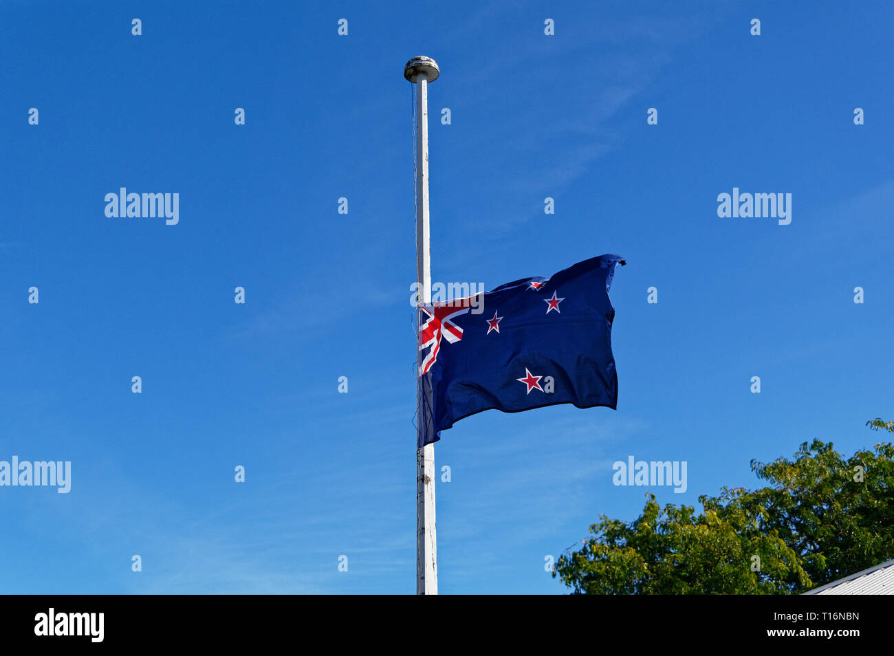 A sign of respect for the fallen, the New Zealand flag flies at half mast - Stock Image