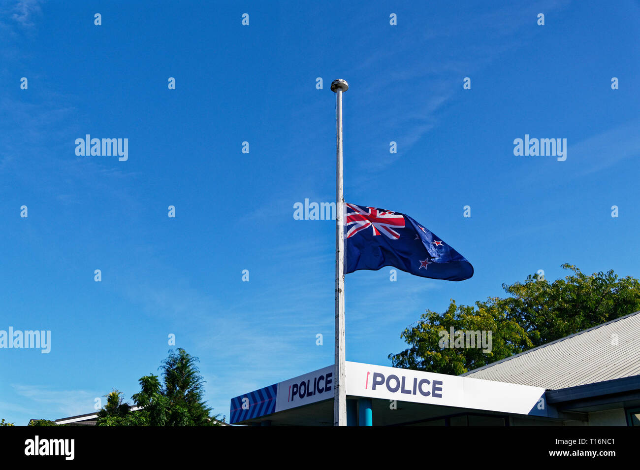 The New Zealand flag flying at half mast outside a police station following the shootings in Christchurch - Stock Image