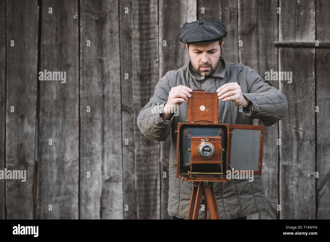 Photographer prepares for shooting and inserts film holder into retro large format camera. Concept - photography of the 1930s-1950s. - Stock Image