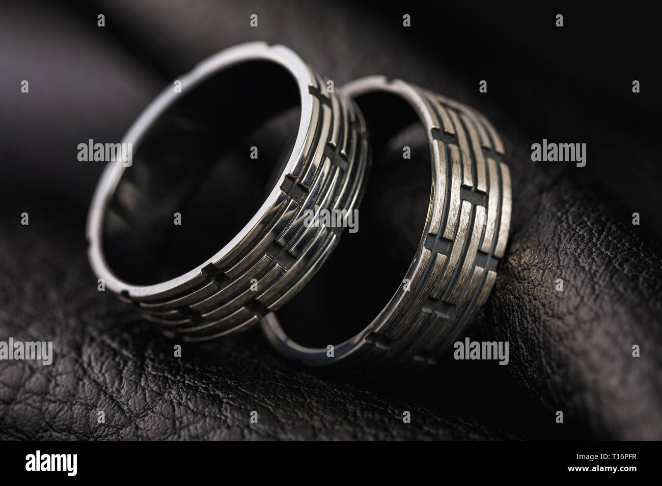 Two mens rings with different processing on a stand made of black leather - Stock Image