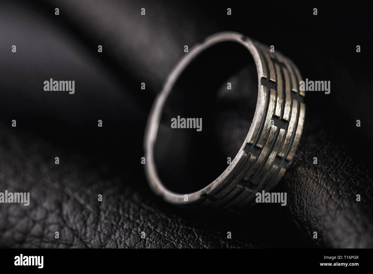 Male ring on a stand made of black leather with copy space - Stock Image