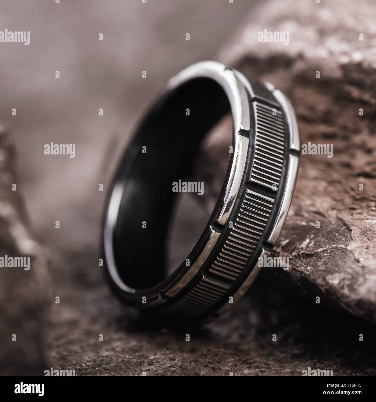 Male silver ring on the background of stones, close-up - Stock Image